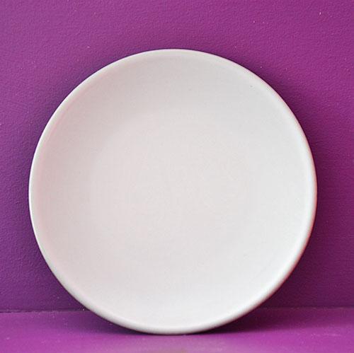 assiette rouge à partager en porcelaine noire et émaillage blanc par les ateliers Revol, fabrication française