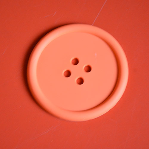ceci n'est pas simplement un bouton, c'est surtout un petit dessous de plat en silicone qui protège vos contenants chauds, comme un dessous de verre en mieux !
