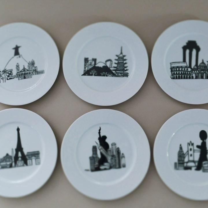 le coffret mini monde comporte 6 assiettes à dessert en porcelaine blanche avec 6 dessins originaux représentant des grandes villes : Paris, New York, Londres, Rome, Tokyo et Rio - création originale d'assiettes et compagnie éditée par la maison revol