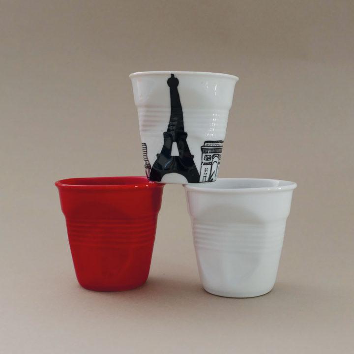 coffret avec la tasse froissée Paris, avec tous les monuments de paris, dessinée par béatrice pene pour le centenaire d'un très célèbre magasin parisien, éditée par la maison de porcelaine Revol, made in france