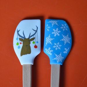 deux mini spatules tovolo de la collection spatulart pour évoquer noel avec le cerf et ses guirlandes et l'imprimé neige.... très pratiques pour cuisiner