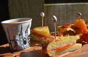 pintxos et tapas à l'espagnole sur une planche family surf avec notamment tortillas aux oignons et chorizo, gaspacho et beignets aux crevettes