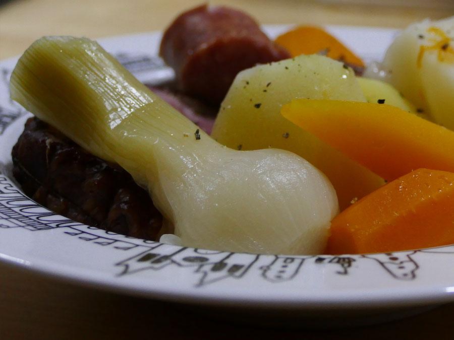 recette de la potée une vrie recette d'hiver avec des carottes multicolores et des patates douces, côté viande, des saucisses fumées, le tout présenté dans une assiette à soupe basque éditée par la manufacture revol, made in france